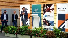 le maire de Vichy en costume sur une estrade devant des kakemonos présentant la nouvelle identité Vichy Economie, deux hommes en fond François Ligier et Romain Chaber