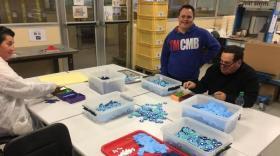 3 travailleurs autour d'une table, assemblent des bleuets en plastique.