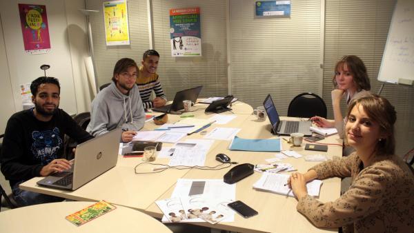 Trois garçons à gauche de l'image derrière des ordinateurs ou en train d'écrire, deux jeunes femmes à droite de l'image autour d'un bureau chargé. tous sont en pleine séance de travail dans un bureau.